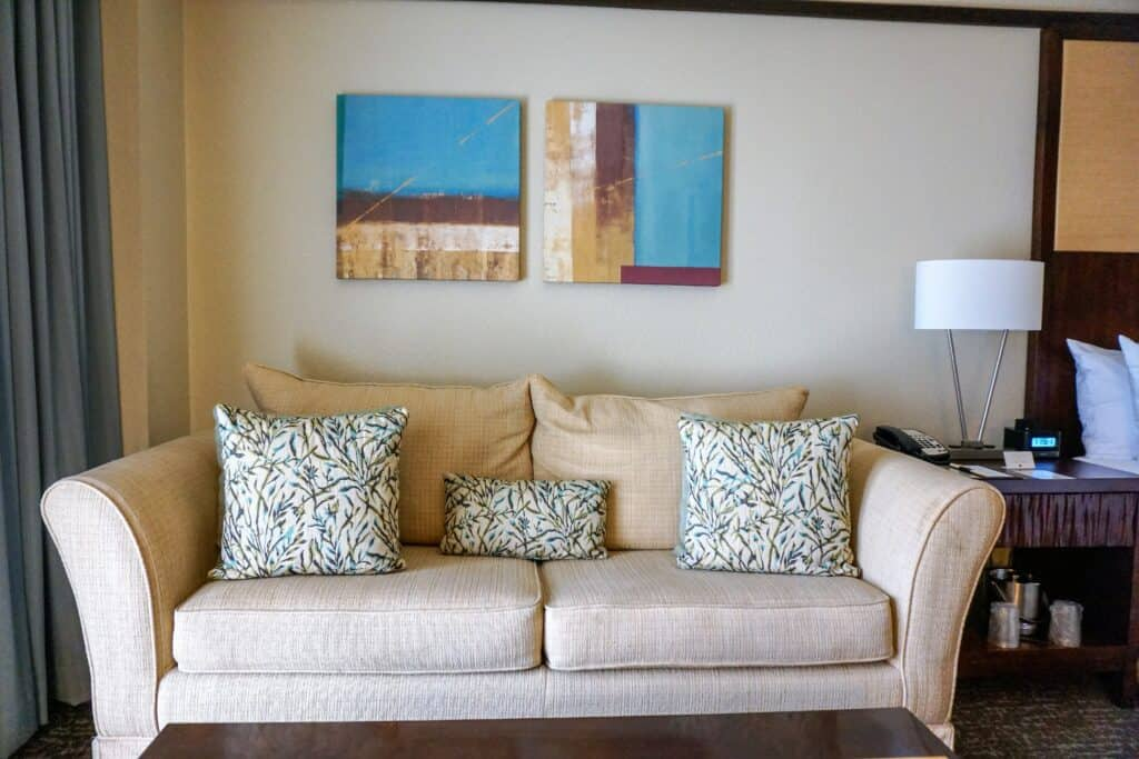 Small sofa with throw pillows underneath pictures on a wall.