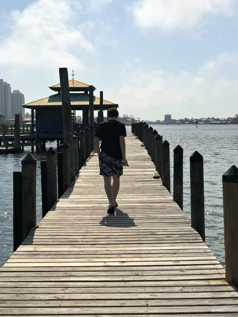 boy walking down a pier