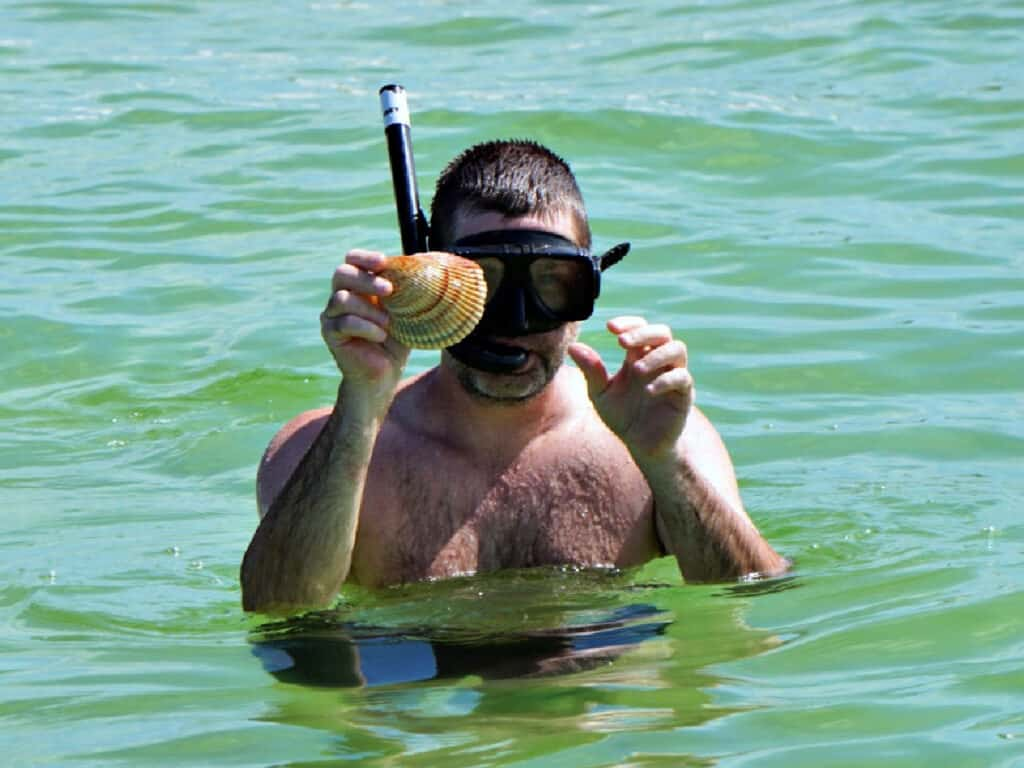 man holding shell in water