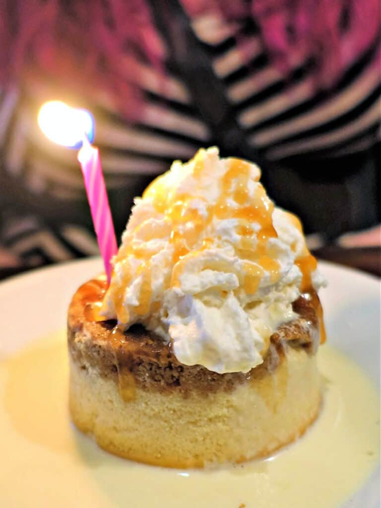 birthday cheesecake with whipped cream and lit candle
