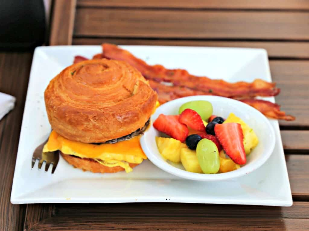 croissanwich, fruit, and bacon on a plate