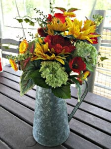 flowers in metal watering pitcher