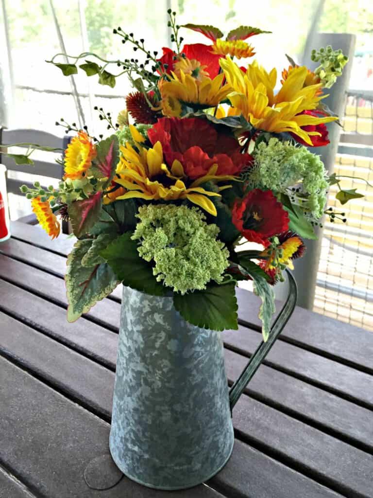 flowers in metal watering pitcher
