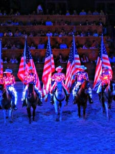 People on horseback holding American flag