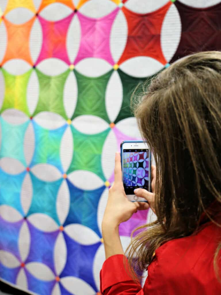 woman taking a picture of a quilt