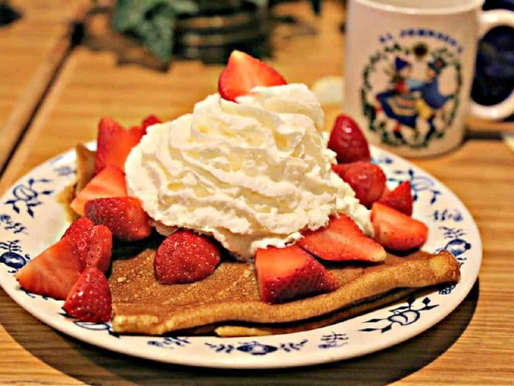 plate of pancakes with whipped cream and strawberries