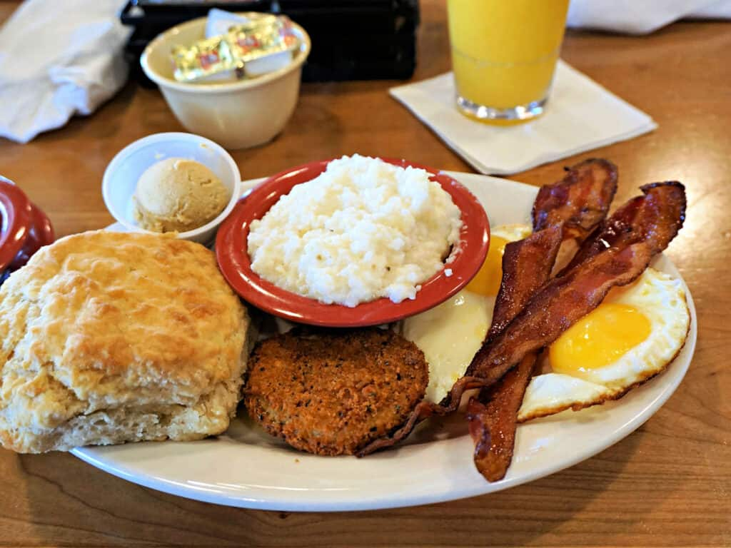 Southern breakfast with biscuit, grits, sausage, bacon, and eggs