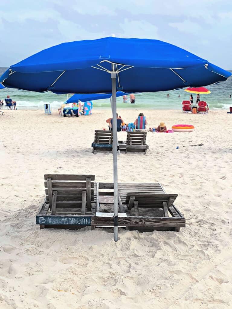 Blue beach umbrella and lounge chairs.