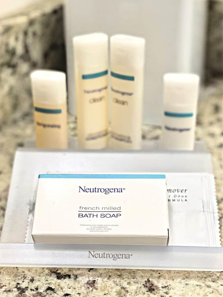 Bar of Neutrogena soap and toiletries on a bath vanity.