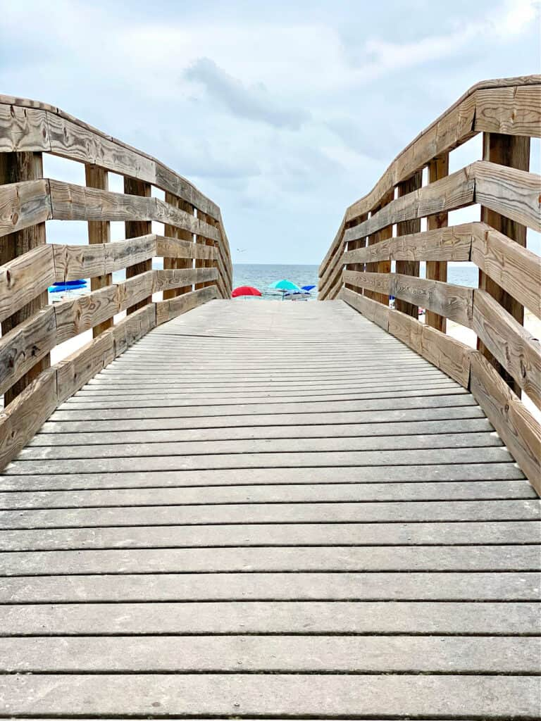 Wooden walkway to beach with umbrellas in the distance.