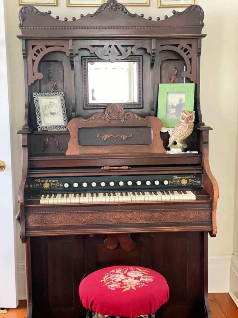 Antique organ with red needlepoint stool.