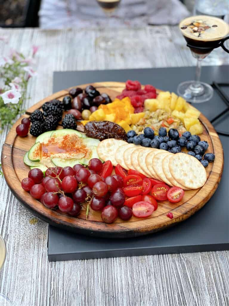 Charcuterie board with fruits, vegetables, and crackers.