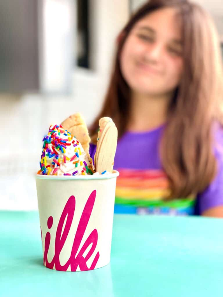 Child looking at dessert cup filled with ice cream and cookie with sprinkles.