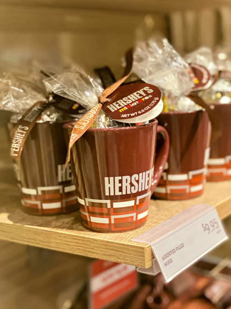 Brown coffee mug filled with Hershey's candy.