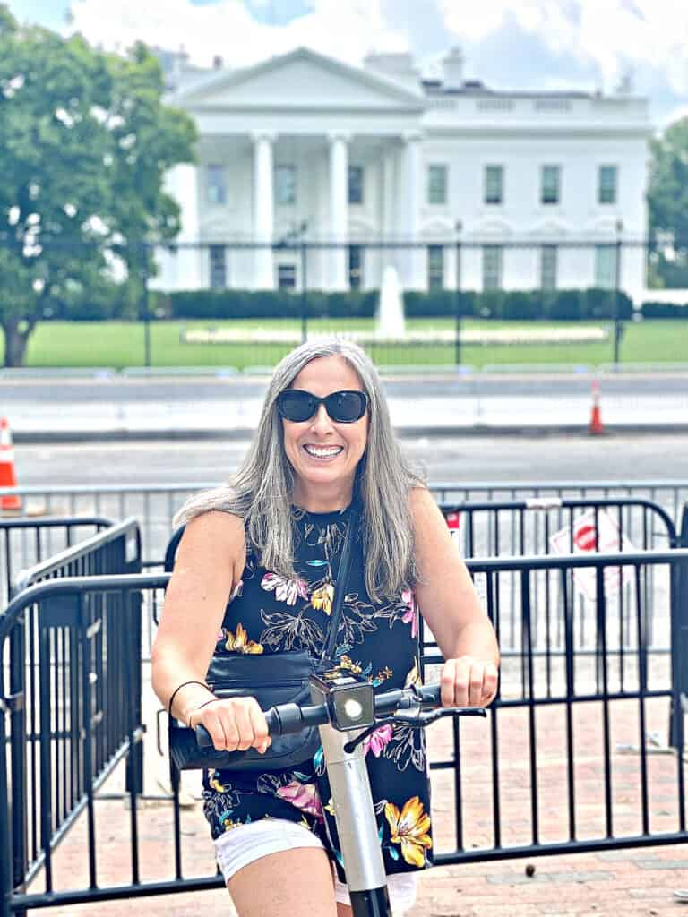 Woman with gray hair on a scooter in front of the White House.