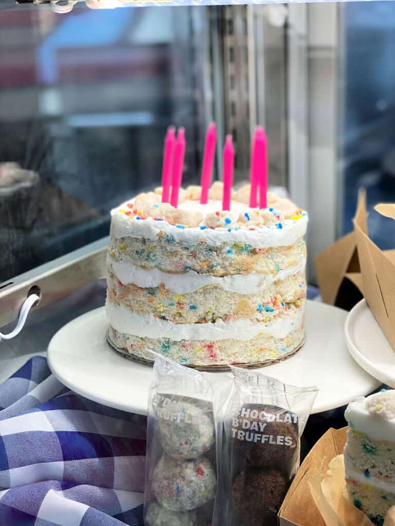 Three layer birthday cake with pink candles.