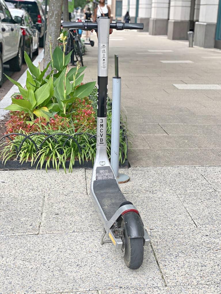 Bird scooter parked on a sidewalk.