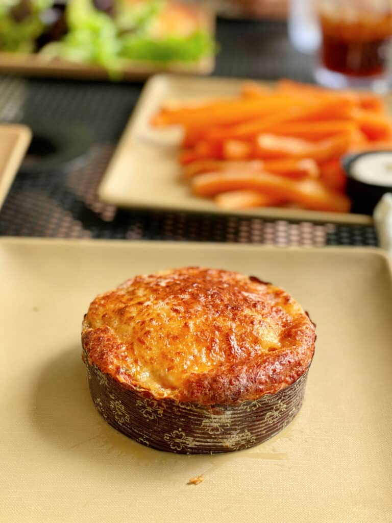 Miniature tomato pie on a plate with carrot fries on the side.