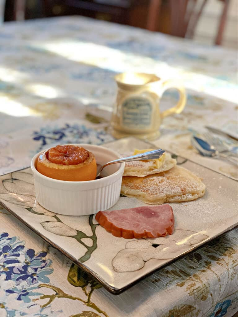 Breakfast plate with ham, baked orange, and pancakes.