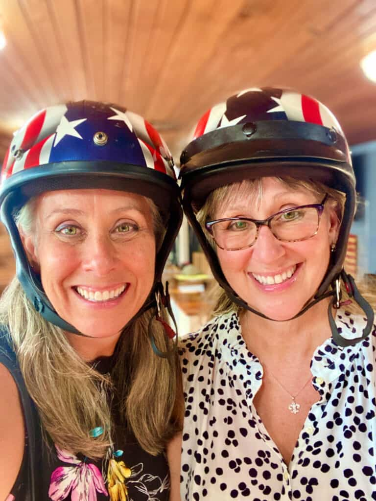 Two women wearing red, white, and bule helmets.