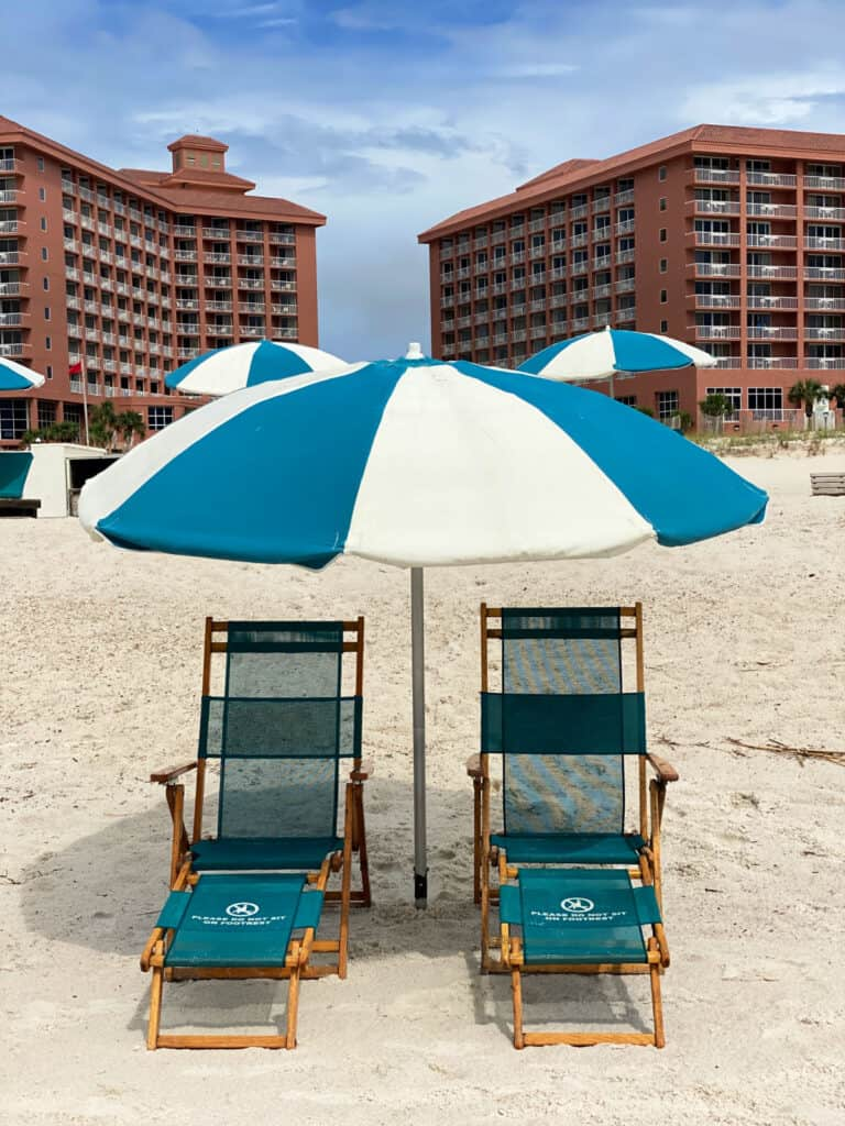 Blue and white umbrella with beach chairs on the beach.