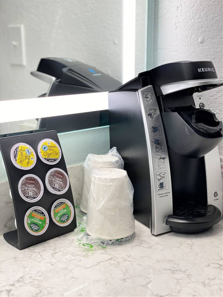 Small Keurig coffee maker, k-cups, and coffee cups.