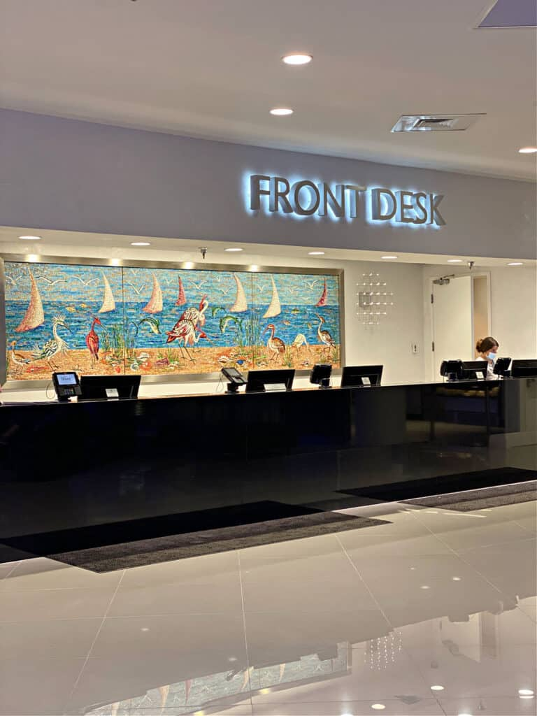 Front desk with woman working and wearing a mask.
