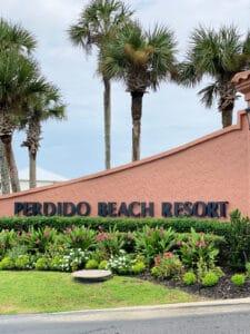 Perdido Beach Resort sign with palm trees.