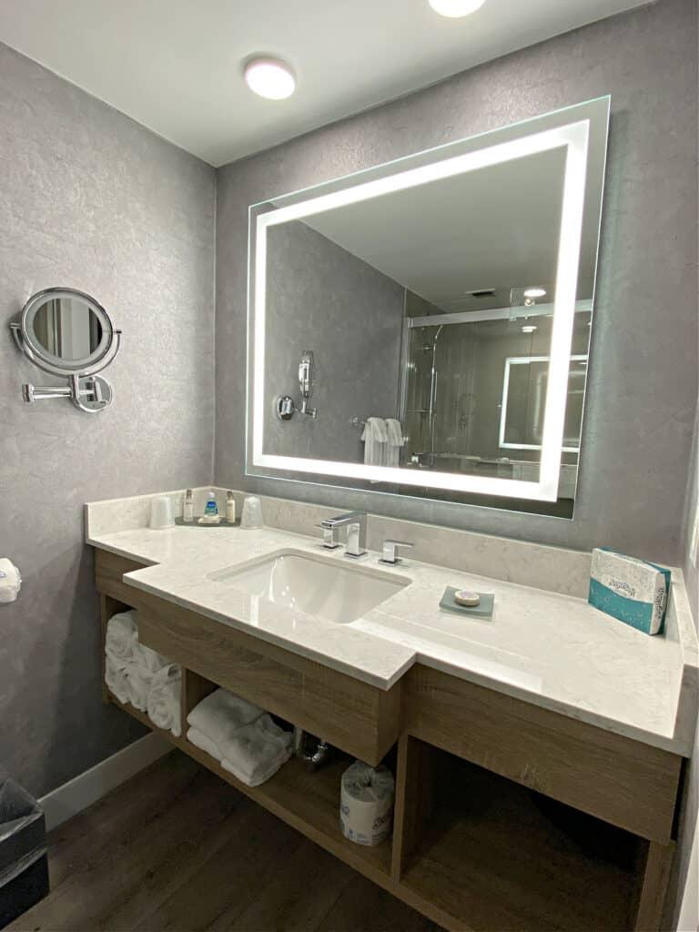 Bathroom sink, vanity, and mirror.