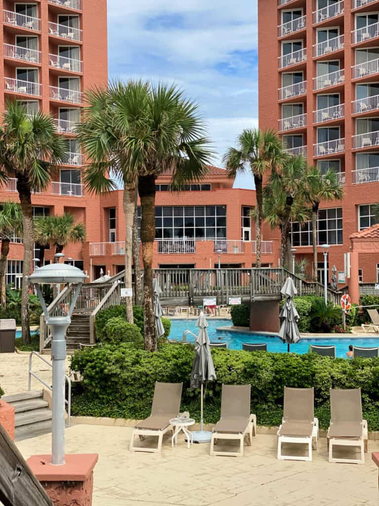 The pool area with lounge chairs and palm trees at Perdido Beach Resort.